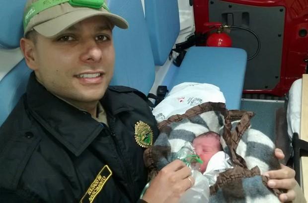 Soldado Nascimento com o bebê socorrido. (foto: Facebook/kleber.p.nascimento)