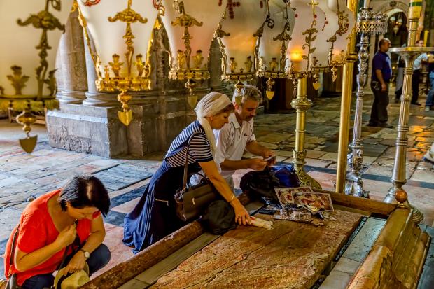 Fiéis rezam diante do local onde o corpo de Jesus teria sido colocado após a crucificação (foto: Bigstock)