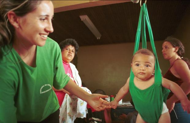 Voluntária da Pastoral da Criança ajudando na pesagem de crianças (foto: divulgação).