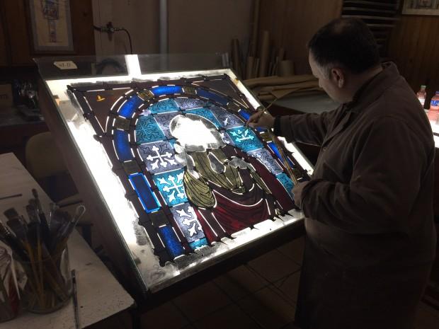 A pintura dos contornos e sombras exige que o vidro seja queimado para que a tinta penetre no material. Foto: Vitrais Zanon.