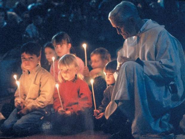 O irmão Roger com algumas crianças em oração.