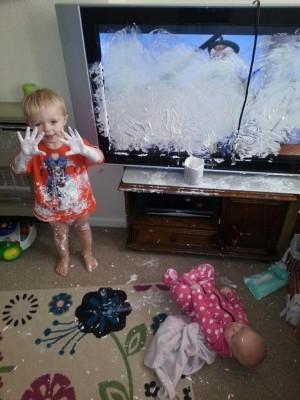 menino com as mãos cheias de pomada após pintar televisão com o produto
